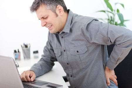 Man having back pain while working.
